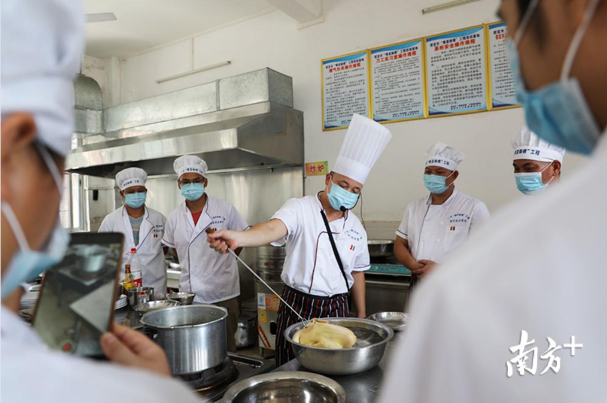 陈东荣正在给学员示范白切鸡的烹饪窍门。