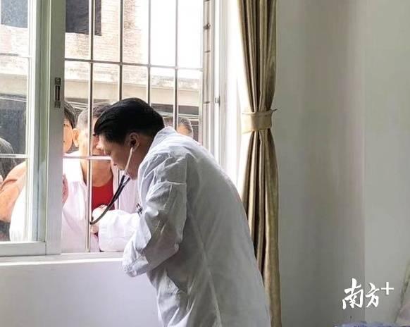 廖新学回乡义诊时被围得水泄不通,当地群众迫不得已透过窗户才能得到他的诊疗。受访者供图
