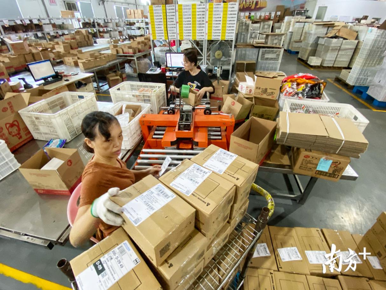 工作人员对照订单快速拣装打包后,一列列快递盒子整装待发。纪金娜 摄
