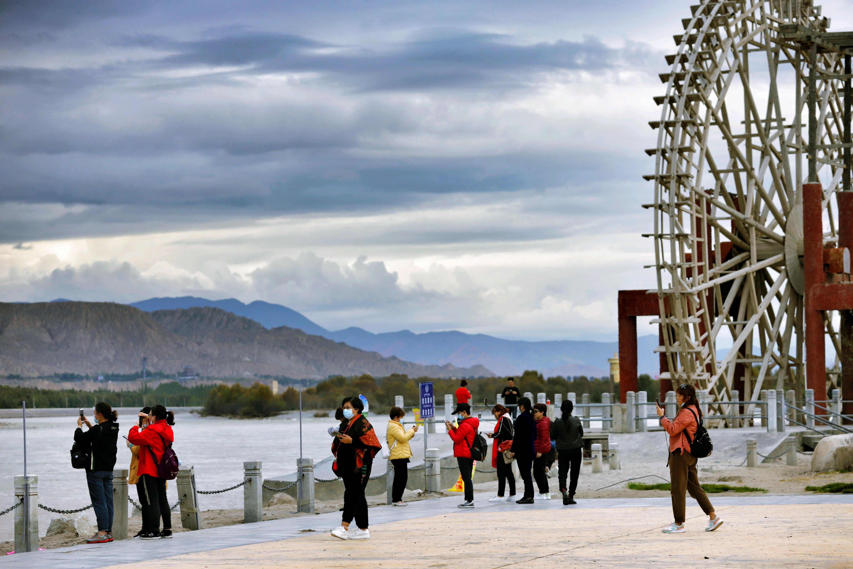 """在青海省贵德县""""网红""""打卡地水车广场,不少游客正在岸边散步、玩耍。"""
