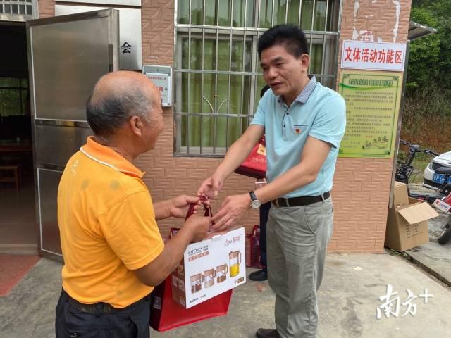 英德市税务局党委书记、局长潘志伟为贫困户送上慰问品。