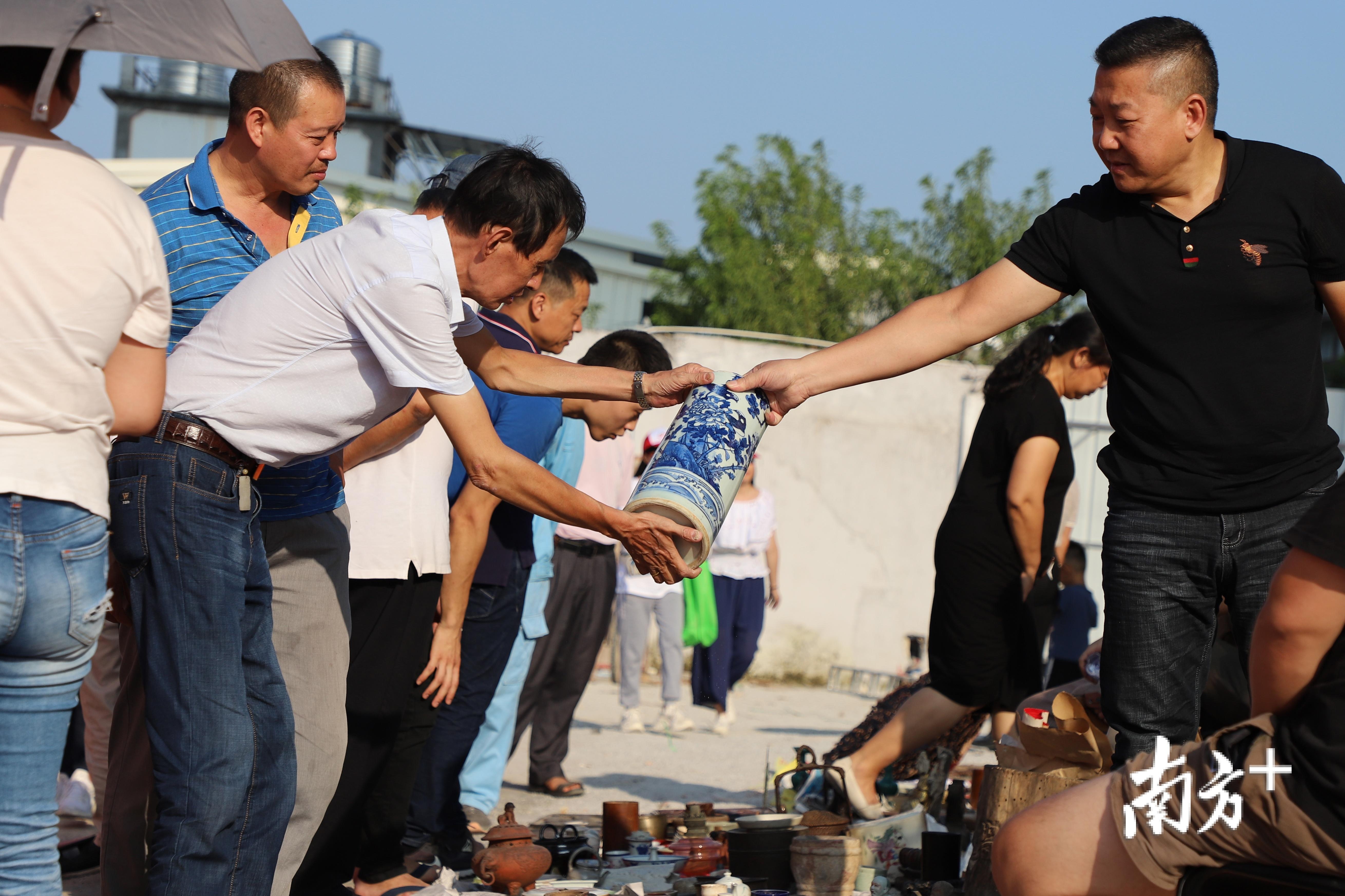 游客与古玩摊主达成交易。