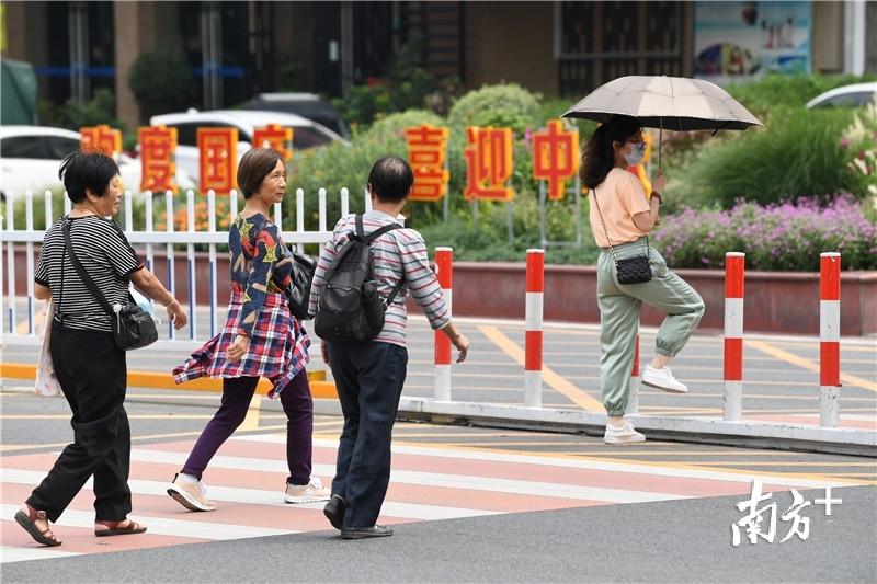 上午一件有点凉,中午两件有点热。街上总能见到手拿衣服的市民。杨兴乐摄
