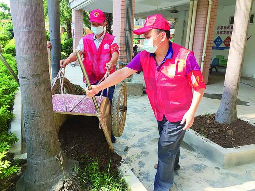 城西街道白沙社区第一书记董立军(左)参与社区环境整治工作。 受访者供图
