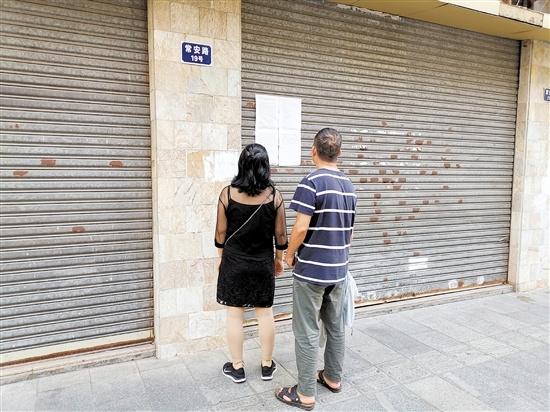 过往市民驻足留意空置商铺的租售信息。
