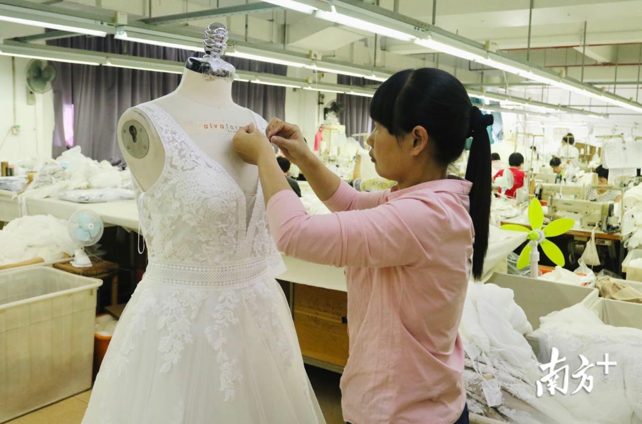 名瑞集团生产车间内,工作人员正在对刚刚完工的婚纱进行修整。黄敏璇 摄