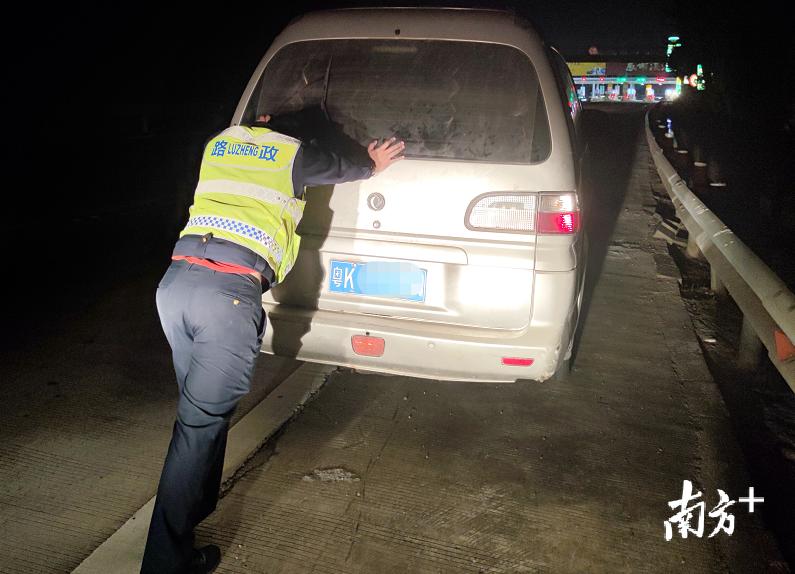2月13日(年初二)晚,茂湛高速官渡路政中队路政员钟进伟帮助故障车司机推车。