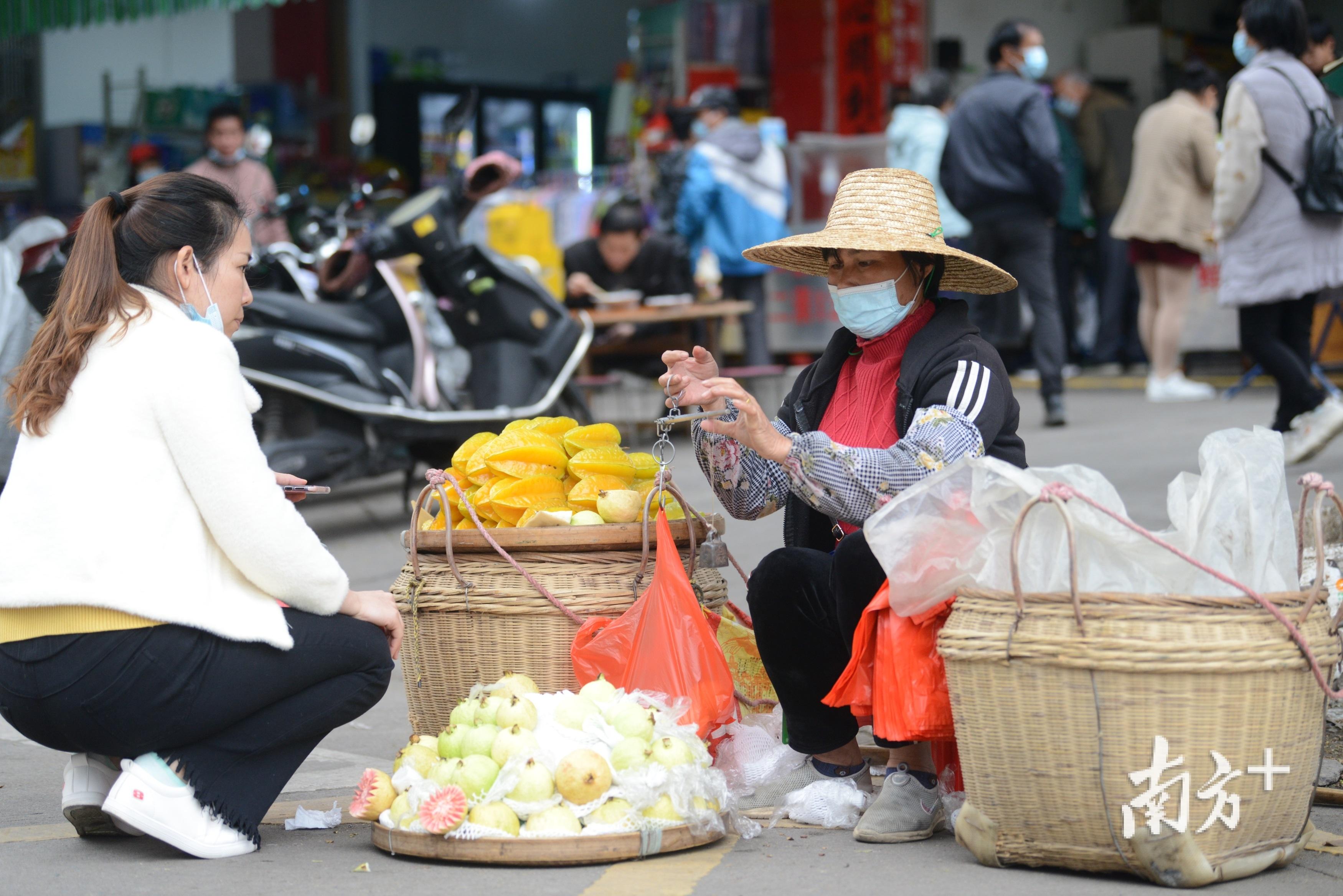 """""""担担军""""罗海燕在广西玉林市摆摊,售卖几小时前刚采摘的阳桃、番石榴。"""