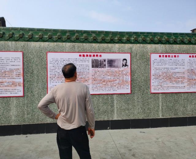 革命烈士林甦的故居林氏祖屋与彭湃故居相邻,林氏祖屋前,游人阅读彭湃和林甦的革命事迹。