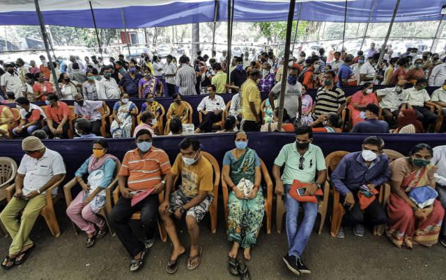 4月26日,众多市民戴着口罩在印度孟买排队等待接种新冠疫苗。新华社发