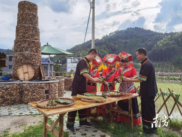 蒙峒古村,身穿少数民族服装的壮瑶群众一边包着粽子,一边用壮语唱起了红歌。