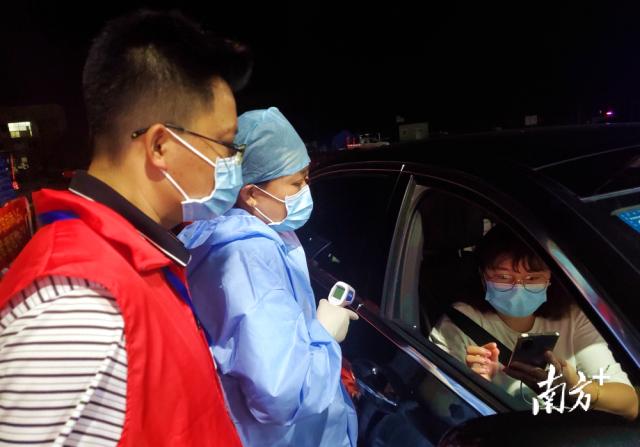 在清连高速星子北上服务区疫情防疫检查点,工作人员对司乘人员进行体温检测,查验健康码、核酸检测证明等情况。