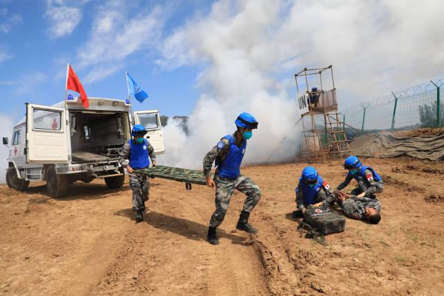 """9月8日,在""""共同命运-2021""""国际维和实兵演习专业分训中,参演官兵在战场救护课目中对""""伤员""""进行战现场急救。新华社发"""