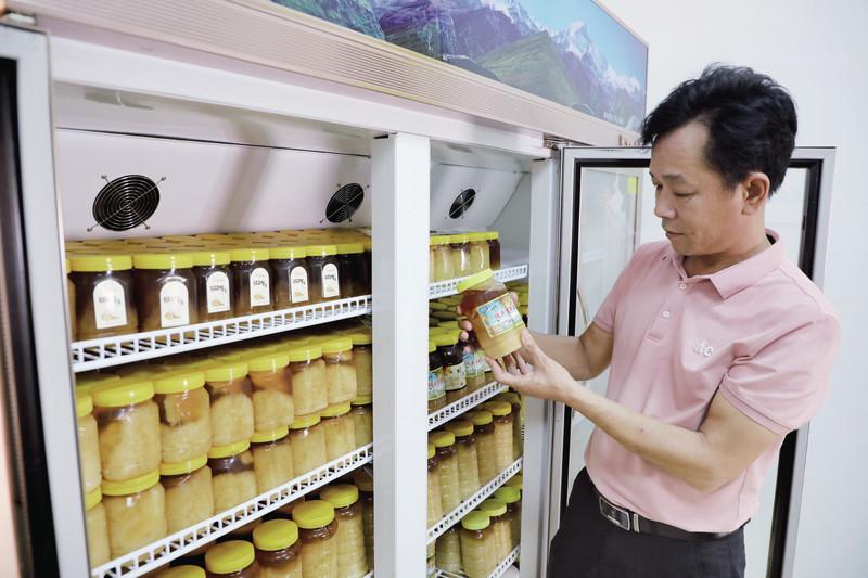 洲仔村村民看着冷藏柜里存放的蜂蜜十分发愁。 西江日报记者 严炯明 摄