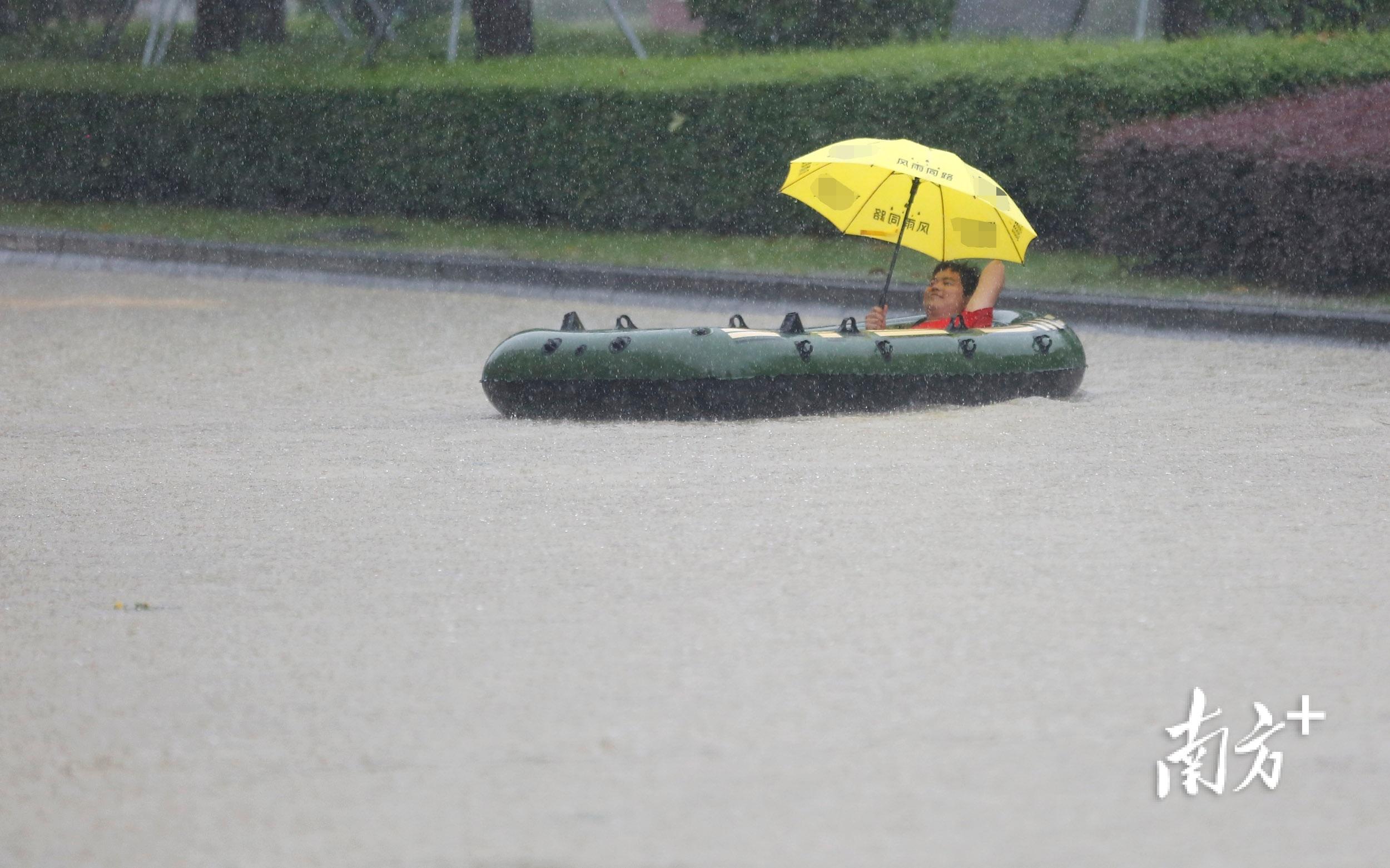 10月10日11时50分,三乡镇景观大道,过街的男子出动橡皮艇。 南方+ 叶志文 摄